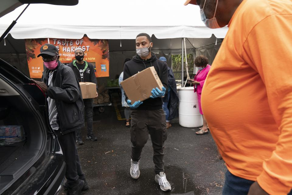 Volunteer Markel Lucas, center, takes a box of food to a patron of the food bank's car, at the Town Hall Education Arts & Recreation Campus (THEARC), Wednesday, Oct. 6, 2021, in Washington. (AP Photo/Jacquelyn Martin)