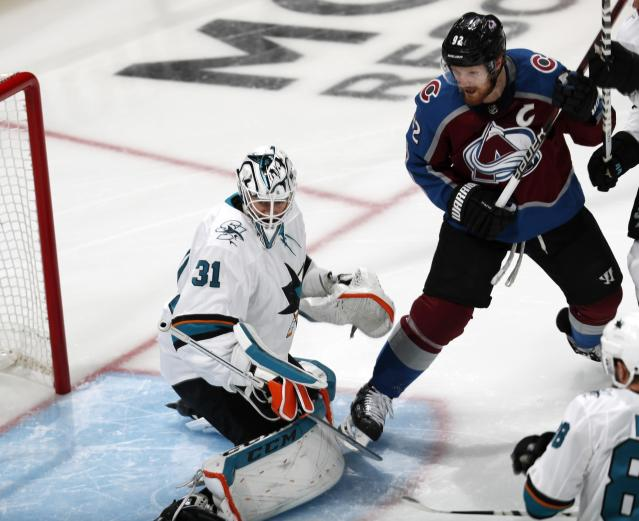 San Jose Sharks goaltender Martin Jones, left, stops a shot by Colorado Avalanche left wing Gabriel Landeskog during the first period of Game 3 of an NHL hockey second-round playoff series Tuesday, April 30, 2019, in Denver. (AP Photo/David Zalubowski)