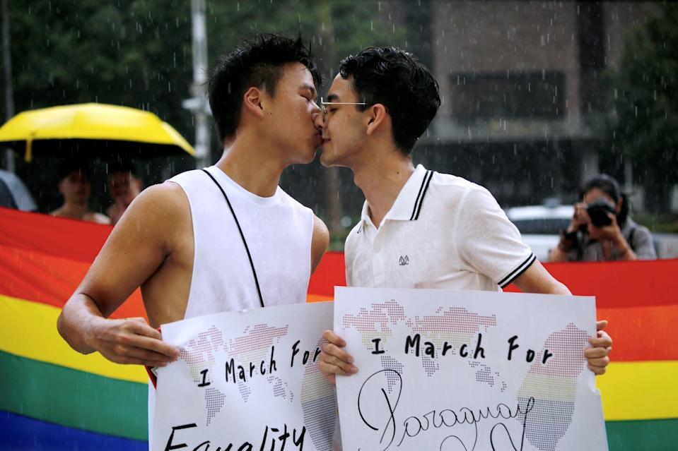 """Participants kiss for a photo during the """"Taiwan Pride Parade For the World"""" rally in Taipei, Taiwan, June 28, 2020."""