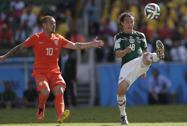 Mexico's Andres Guardado controls the ball next to Netherlands' Wesley Sneijder during the World Cup round of 16 soccer match between the Netherlands and Mexico at the Arena Castelao in Fortaleza, Brazil, Sunday, June 29, 2014. (AP Photo/Marcio Jose Sanchez)