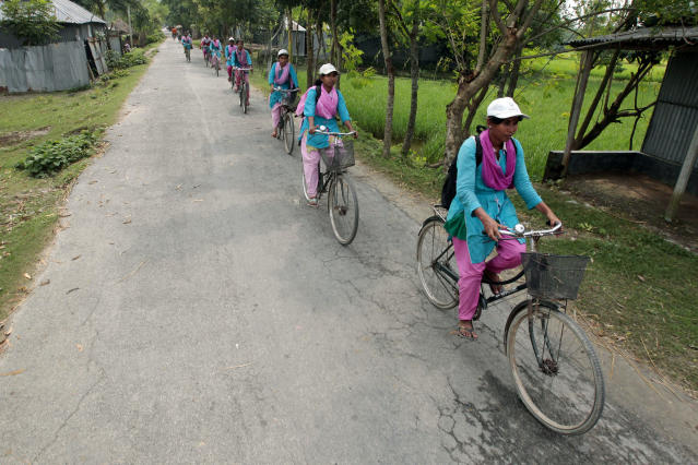 """In this Sept. 30, 2012 photo, """"Info Ladies"""" pedal their way to Saghata, a remote impoverished farming village in Gaibandha district, 190 kilometers (120 miles) north of Dhaka, Bangladesh. Dozens of """"Info Ladies"""" bike into remote Bangladeshi villages with laptops and Internet connections, helping tens of thousands of people _ especially women - get everything from government services to chats with distant loved ones. They've expanded access to vital computer services in a country where only 5 million of 152 million people have Internet access. (AP Photo/A.M. Ahad)"""