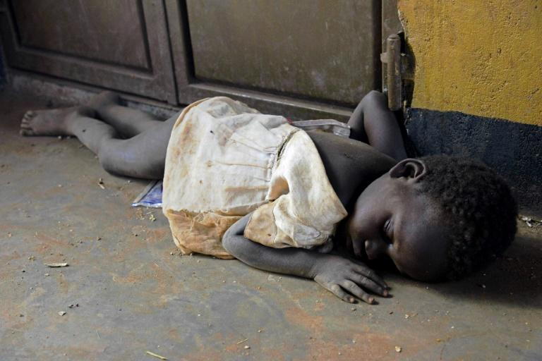 A child refugee sleeps on a floor after arriving in Uganda from South Sudan