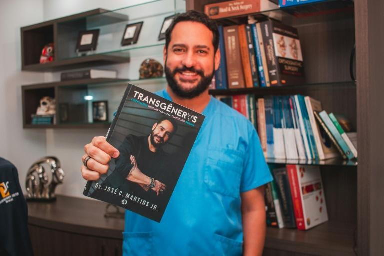 This handout picture released by the Transgender Centre Brazil shows Brazilian doctor Jose Martins posing for a picture as he holds a book about transgender people written by him, in Blumenau, Brazil, on July 8, 2020