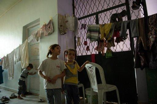 Two Syrian girls from Aleppo stand next to hanging laundry in a school being used to shelter displaced people in the town of Azaz, north of Aleppo, on August 11. The Syrian army has pounded rebel strongholds in Damascus province, where more than 45 people, including 36 civilians, have been killed in the past 48 hours, a watchdog said