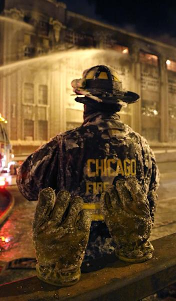 The frozen ice covered pair of gloves belonging to a Chicago firefighter stand on a railing behind him in single digit temperatures during a five-alarm blaze in a warehouse on the city's South Side, Bridgeport neighborhood rages Wednesday, Jan. 23, 2013, in Chicago. (AP Photo/Charles Rex Arbogast)