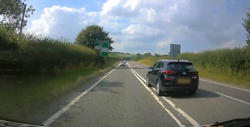 This motorist was caught on dashcam overtaking another car by crossing double white lines (Dorset Police/PA).