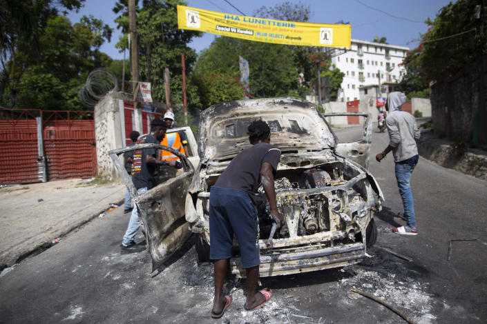 People try to recover usable material from a burned-out car during a protest a day after the murder of President Jovenel Moise, in Port-au-Prince, Haiti, Thursday, July 8, 2021. Moise was assassinated after a group of armed men attacked his private residence, and gravely wounding his wife, First Lady Martine Moise. (AP Photo/Joseph Odelyn)