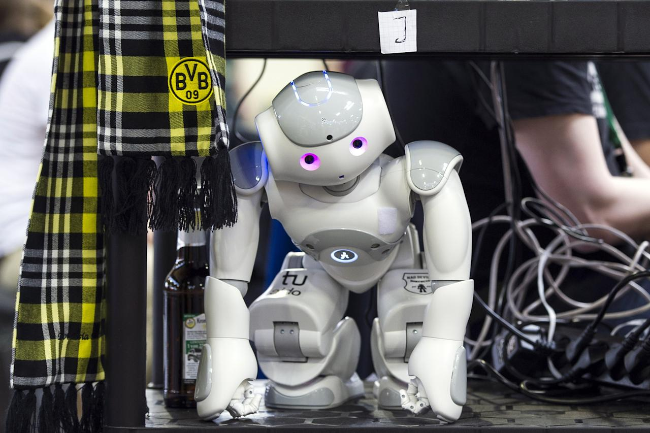 MAGDEBURG, GERMANY - APRIL 26:  A robot stands on a shelf near the play field at the 2013 RoboCup German Open tournament on April 26, 2013 in Magdeburg, Germany. The robots, which are a model called Nao, manufactured by Aldebaran Robotics, perform autonomously and communicate with one another via WLAN. The three-day tournament is hosting 43 international teams and 158 German junior teams that compete in a variety of disciplines, including soccer, rescue and dance.  (Photo by Jens Schlueter/Getty Images)