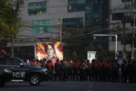 A large banner with an image of deposed Myanmar leader Aung San Suu Kyi faces rows of policemen blocking the road near the headquarters of the National League for Democracy party in Yangon, Myanmar Monday, Feb. 15, 2021. Security forces in Myanmar intensified their crackdown against anti-coup protesters on Monday, seeking to quell the large-scale demonstrations calling for the military junta that seized power earlier this month to reinstate the elected government. (AP Photo)