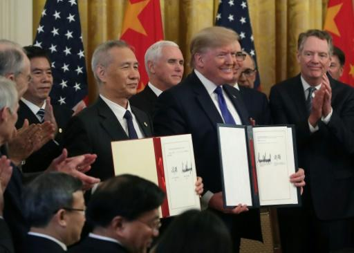 "US President Donald Trump (pictured January 15, 2020) and Chinese Vice Premier�Liu�He hold up signed agreements of ""phase one"" of a trade deal between the two countries"
