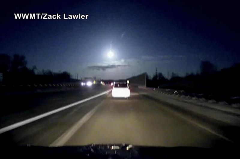 A dash cam video shows a brightly-lit object fall from the sky above the highway. (AP)