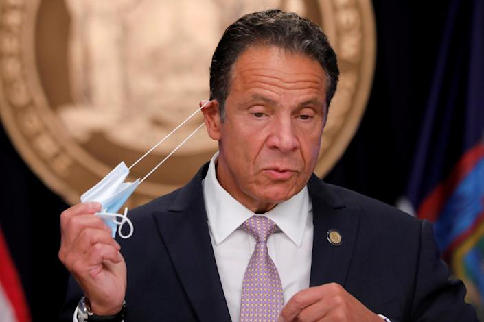 New York Governor Andrew Cuomo removes his protective face mask as he arrives to speak during a daily briefing following the outbreak of the coronavirus disease (COVID-19) in Manhattan in New York City, New York, U.S., July 13, 2020. REUTERS/Mike Segar     TPX IMAGES OF THE DAY