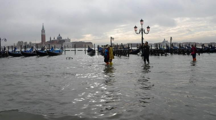 People walk in high water, in Venice, Italy, Wednesday, Nov. 13, 2019. (AP Photo)