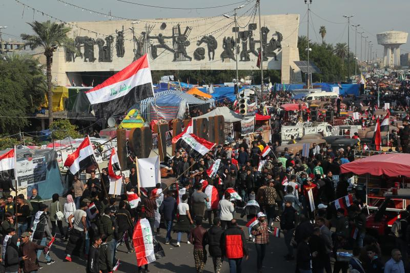 Hundreds of people march inside Tahrir Square carrying national flags and chanting religious slogans in Baghdad, Iraq, Thursday, Dec. 5, 2019. Anti-government protesters say multiple people have suffered stab wounds in Baghdad's Tahrir Square, the epicenter of their movement, after political parties and Iran-backed militia groups briefly joined them, raising fears of infiltration by authorities. (AP Photo/Hadi Mizban)