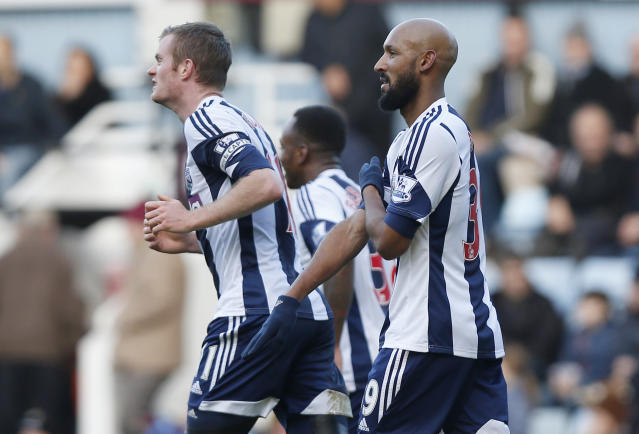 """FILE - This Saturday Dec. 28, 2013 file photo shows West Bromwich Albion's Nicolas Anelka, right, as he gestures to celebrate his goal against West Ham United during their English Premier League soccer match at Upton Park, London. West Bromwich Albion striker Nicolas Anelka was charged by the English Football Association on Tuesday Jan 21, 2014 for performing a racially aggravated gesture considered to be anti-Semitic while celebrating a Premier League goal. The gesture, which is known in France as a """"quenelle"""" and has been described as an """"inverted Nazi salute,"""" was performed by Anelka in the Dec. 28 game against West Ham. (AP Photo/Sang Tan, File)"""