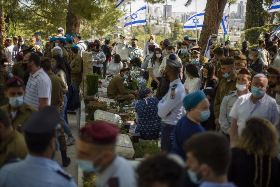 Civilians and soldiers gather by graves of Israeli soldiers during a Memorial Day ceremony for fallen soldiers and victims of attacks, at the military cemetery at Mount Herzl, in Jerusalem, Wednesday, April 14, 2021. On Israel Memorial Day, the most solemn day on Israel's national calendar, people stood at attention while a two-minute siren sounded around the country and held remembrance ceremonies at cemeteries. (AP Photo/Ariel Schalit)