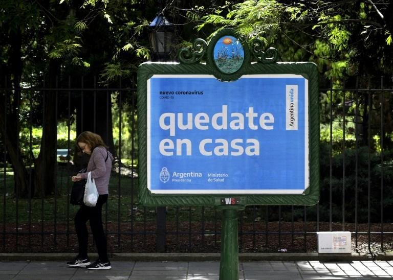 """A woman walks near an Argentine health ministry sign in Buenos Aires that reads """"Stay at home"""""""