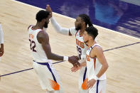 Phoenix Suns forward Jae Crowder (99) celebrates with guard Devin Booker and center Deandre Ayton (22) during the first half of an NBA basketball game against the Houston Rockets, Monday, April 12, 2021, in Phoenix. (AP Photo/Matt York)