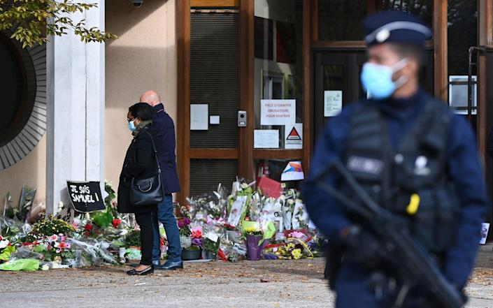 People look at flowers in France laid in homage to slain history teacher Samuel Paty - ANNE-CHRISTINE POUJOULAT/AFP