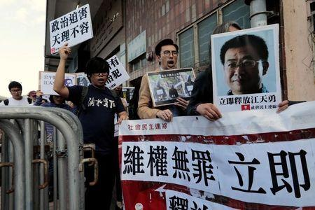 Pro-democracy demonstrators hold up portraits of Chinese disbarred lawyer Jiang Tianyong, demanding his release, during a demonstration outside the Chinese liaison office in Hong Kong