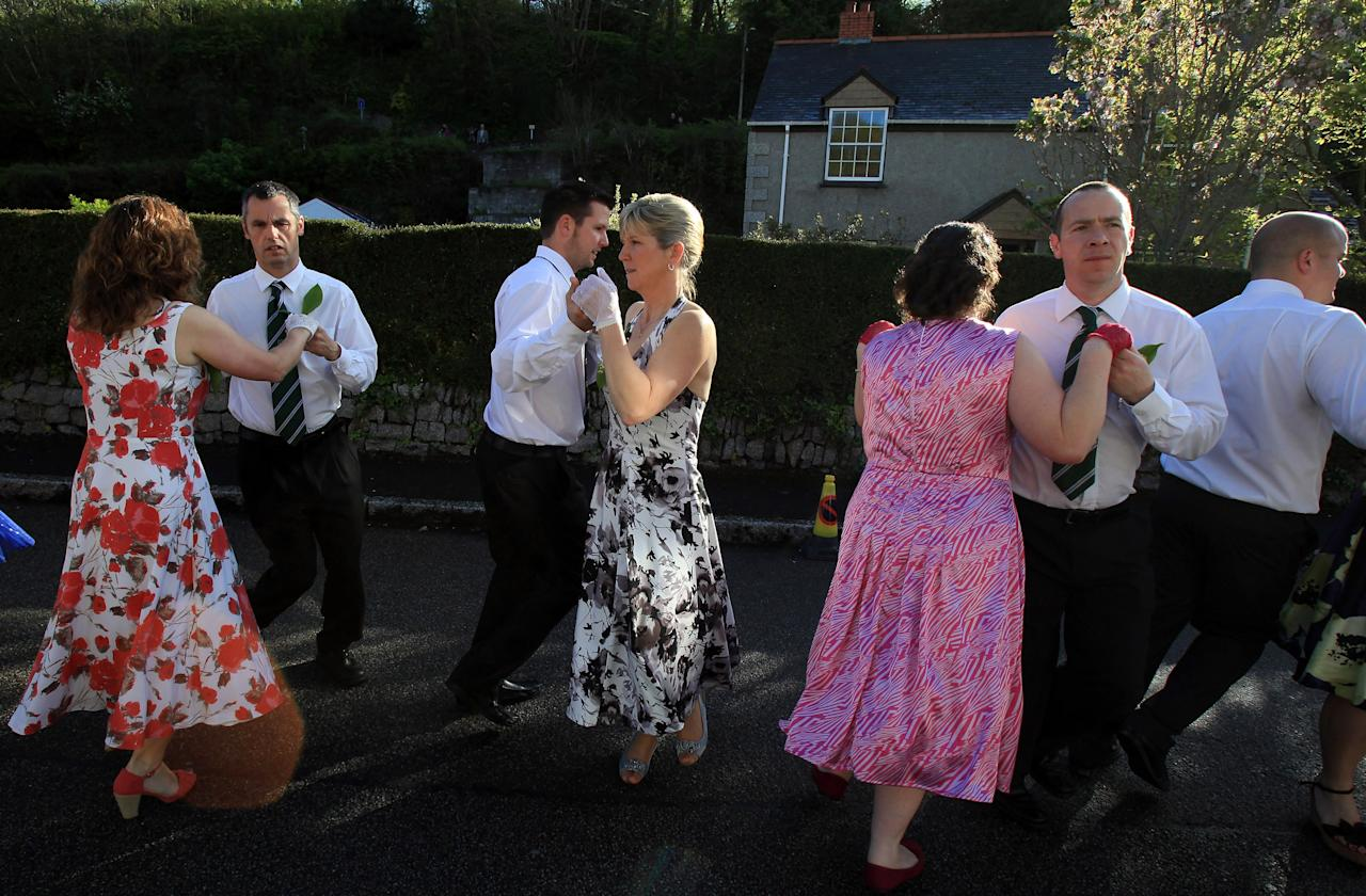 HELSTON, ENGLAND - MAY 08:  People dance in the early morning light as they take part in the Early Morning Dance as part of the Helston Flora Day celebrations on May 8, 2012 in Helston, England. The dance, which starts at 7am and is the first in a series throughout the day, goes all over the town and even in and out of private houses and shops. Helston Flora Day is one of the UK's oldest customs still practised today and is said to be a celebration of the passing of Winter and the arrival of Spring. However the highlight is the midday dance which was traditionally the dance of the gentry in the town and is why men still wear top hats and tails while the women dance in their finest dresses. (Photo by Matt Cardy/Getty Images)