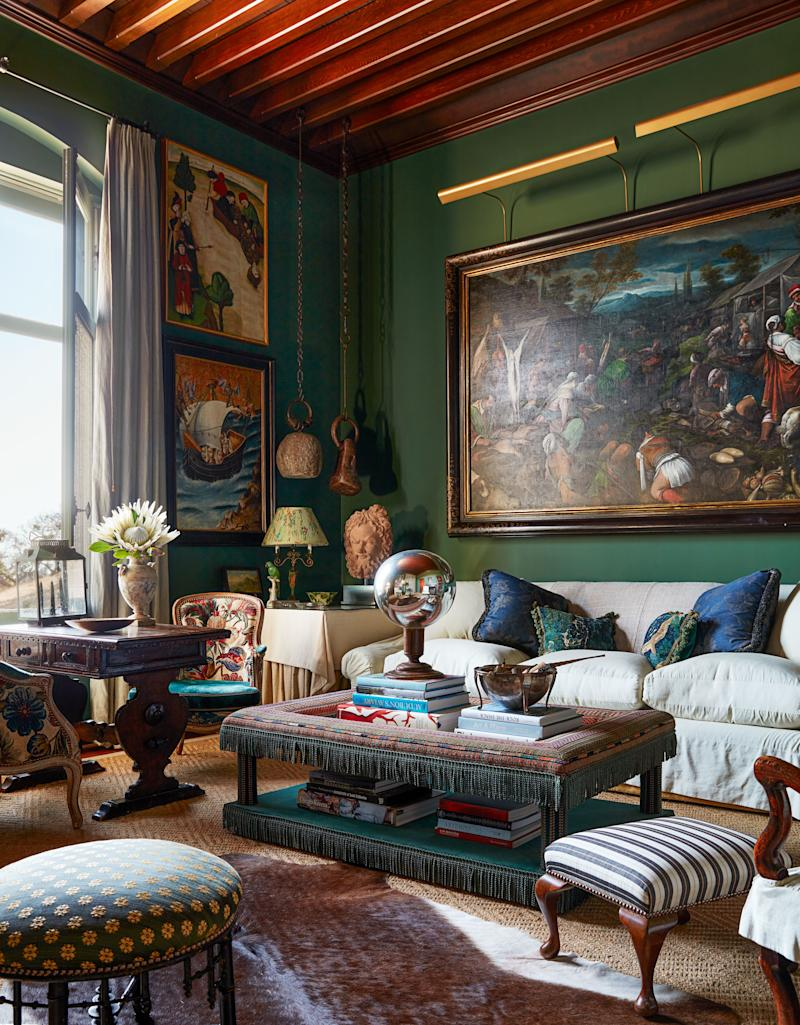 In a green-walled sitting room, a sofa wearing a Threads linen-blend converses with a cocktail table from Richard Shapiro Studiolo and two ottomans upholstered in horsehair fabrics by Stark.