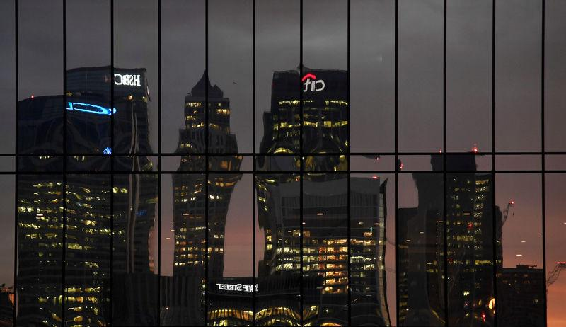 FILE PHOTO: The Canary Wharf business district is seen reflected in windows at dusk in London