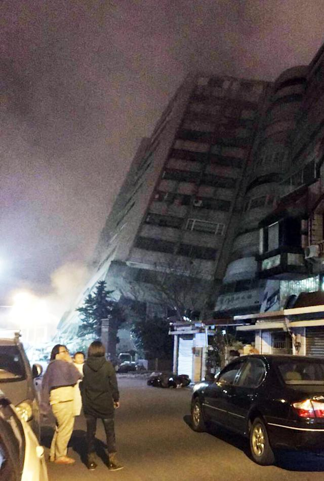<p>In this photo released by Hualien County Fire Bureau, Taiwanese people watching a building that collapsed on its side from an early morning earthquake in Hualien County, eastern Taiwan, early Feb. 7 2018. (Photo: Hualien County Fire Bureau via AP) </p>
