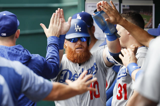 Los Angeles Dodgers' Justin Turner (10) celebrates in the dugout after scoring on an RBI single by Yasmani Grandal off Cincinnati Reds relief pitcher Wandy Peralta in the fifth inning of a baseball game, Wednesday, Sept. 12, 2018, in Cincinnati. (AP Photo/John Minchillo)