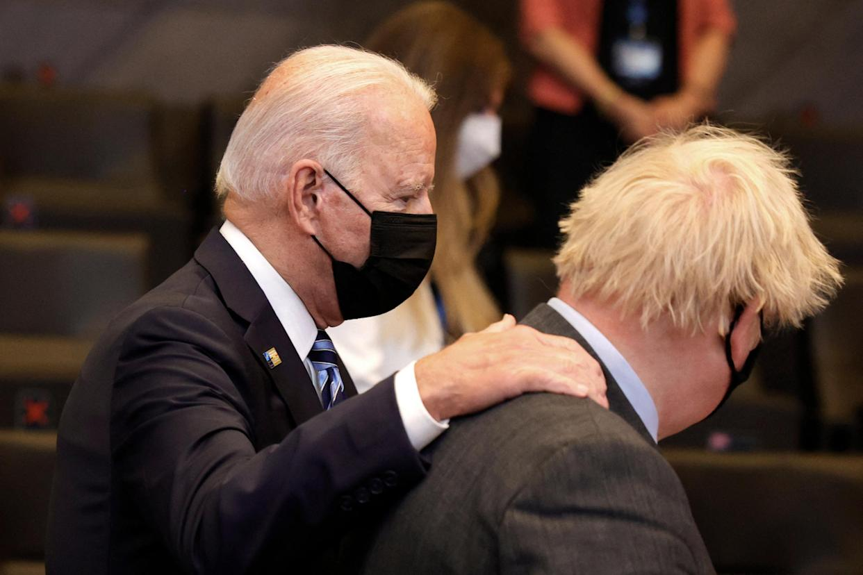 US President Joe Biden (L) greets Britain's Prime Minister Boris Johnson during a plenary session of a NATO summit at the North Atlantic Treaty Organization (NATO) headquarters in Brussels, on June 14, 2021. - The allies will agree a statement stressing common ground on securing their withdrawal from Afghanistan, joint responses to cyber attacks and relations with a rising China. (Photo by Olivier Matthys / POOL / AFP) (Photo by OLIVIER MATTHYS/POOL/AFP via Getty Images)