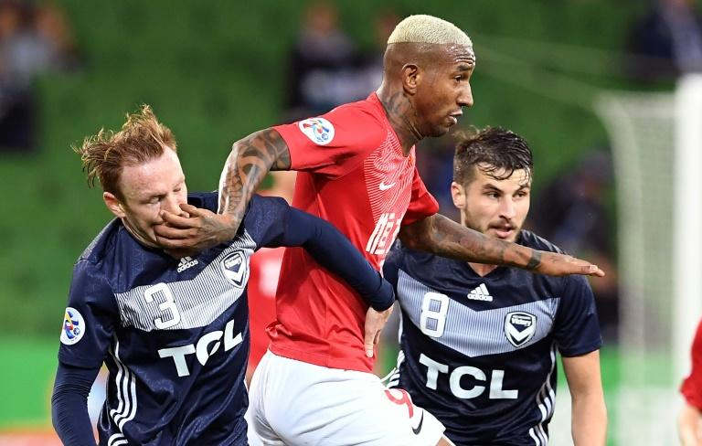 Guangzhou's Anderson Talisca fends off Melbourne Victory's Corey Brown (left) and Terry Antonis