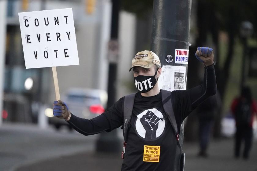 A protester displays a sign in front of the CNN center Wednesday, Nov. 4, 2020 in Atlanta. (AP Photo/John Bazemore)