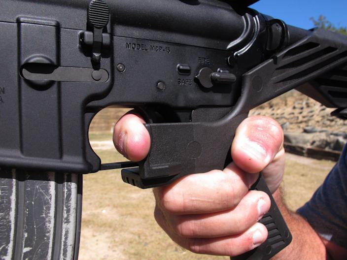 """In this Oct. 4, 2017, file photo, shooting instructor Frankie McRae demonstrates the grip on an AR-15 rifle fitted with a """"bump stock"""" at his 37 PSR Gun Club in Bunnlevel, N.C. The devices were used by Stephen Paddock when he opened fire on a country music festival in Las Vegas, killing dozens of people."""