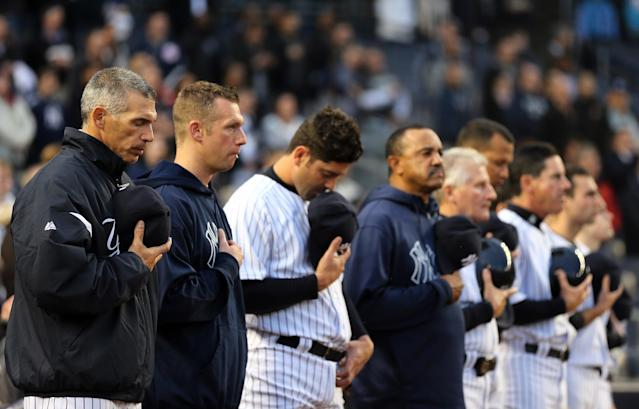 NEW YORK, NY - APRIL 16: Manager Joe Girardi of the New York Yankees observes a moment of silence to honor the victims of the Boston Marathon bombing on April 16, 2013 at Yankee Stadium in the Bronx borough of New York City. All uniformed team members are wearing jersey number 42 in honor of Jackie Robinson Day. (Photo by Elsa/Getty Images)