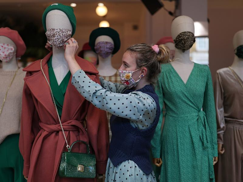 A shop stylist adjusts a face mask on a mannequin in a window display at fashion store ¯ST London, after a range of new coronavirus restrictions came into place in England. (Yui Mok/PA)