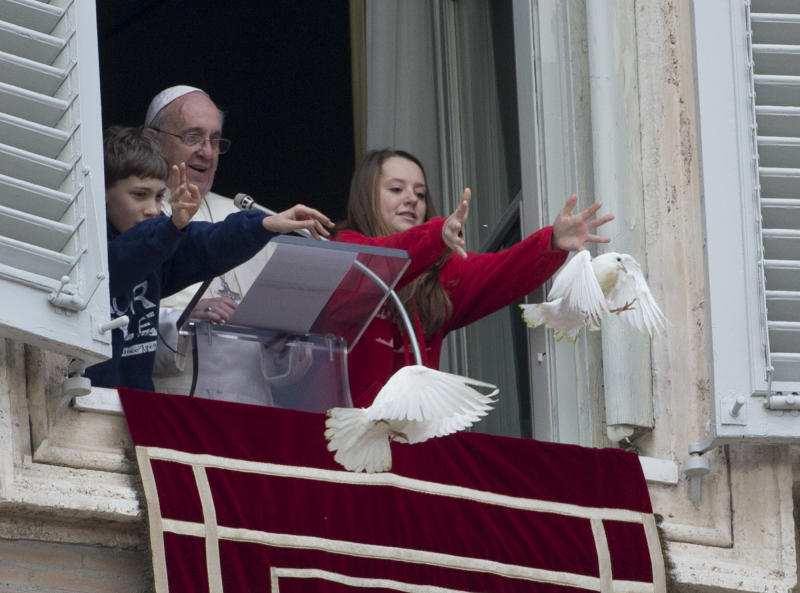 """Pope Francis looks at two children as they free doves during the Angelus prayer he celebrated from the window of his studio overlooking St. Peter's Square, at the Vatican, Sunday, Jan. 26, 2014. Pope Francis has called for """"constructive dialogue"""" between Ukraine's authorities and its people, urging all to renounce violence in the upheaval convulsing their country. Speaking from a window of the Apostolic Palace in the Vatican to thousands of faithful in St. Peter's Square, Francis said he was praying for Ukraine, especially for those who have lost their lives in recent days. He appealed on Sunday for """"the spirit of peace and the search for the common good"""" to prevail in the eastern European nation. (AP Photo/Gregorio Borgia)"""
