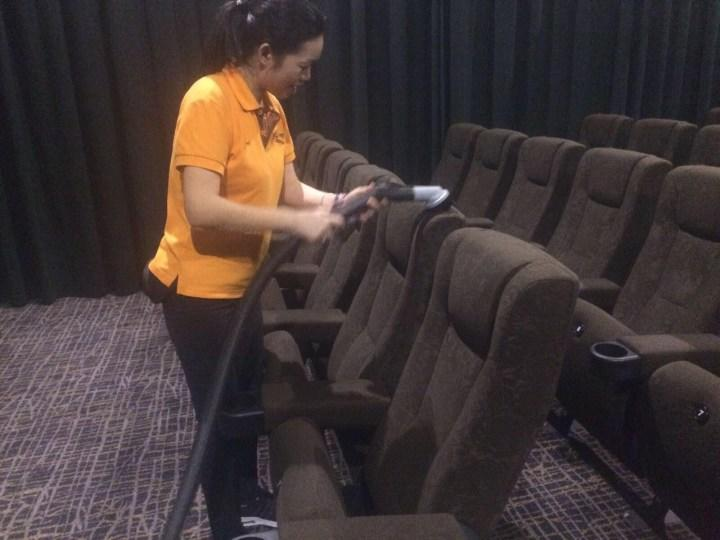 Armed with a vacuum cleaner and the appropriate attachments, she cleans the entire surface of every seat in the cinema halls.