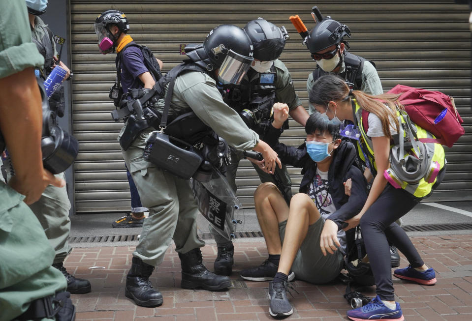 A reporter is helped by police and others after being with sprayed pepper spray in Causeway Bay before the annual handover march in Hong Kong, Wednesday, July. 1, 2020. Hong Kong marked the 23rd anniversary of its handover to China in 1997, and just one day after China enacted a national security law that cracks down on protests in the territory. (AP Photo/Vincent Yu)