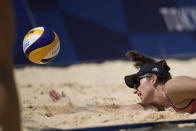 Sarah Sponcil, of the United States, dives for the ball during a women's beach volleyball match against Canada at the 2020 Summer Olympics, Sunday, Aug. 1, 2021, in Tokyo, Japan. (AP Photo/Felipe Dana)