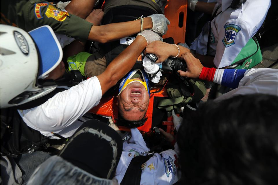 An injured reporter is taken to an ambulance during clashes between the police and anti-government protesters near the Government House in Bangkok February 18, 2014. A Thai police officer was killed and dozens of police and anti-government protesters were wounded in gun battles and clashes in Bangkok on Tuesday, officials and witnesses said. REUTERS/Damir Sagolj (THAILAND - Tags: SOCIETY CIVIL UNREST POLITICS)