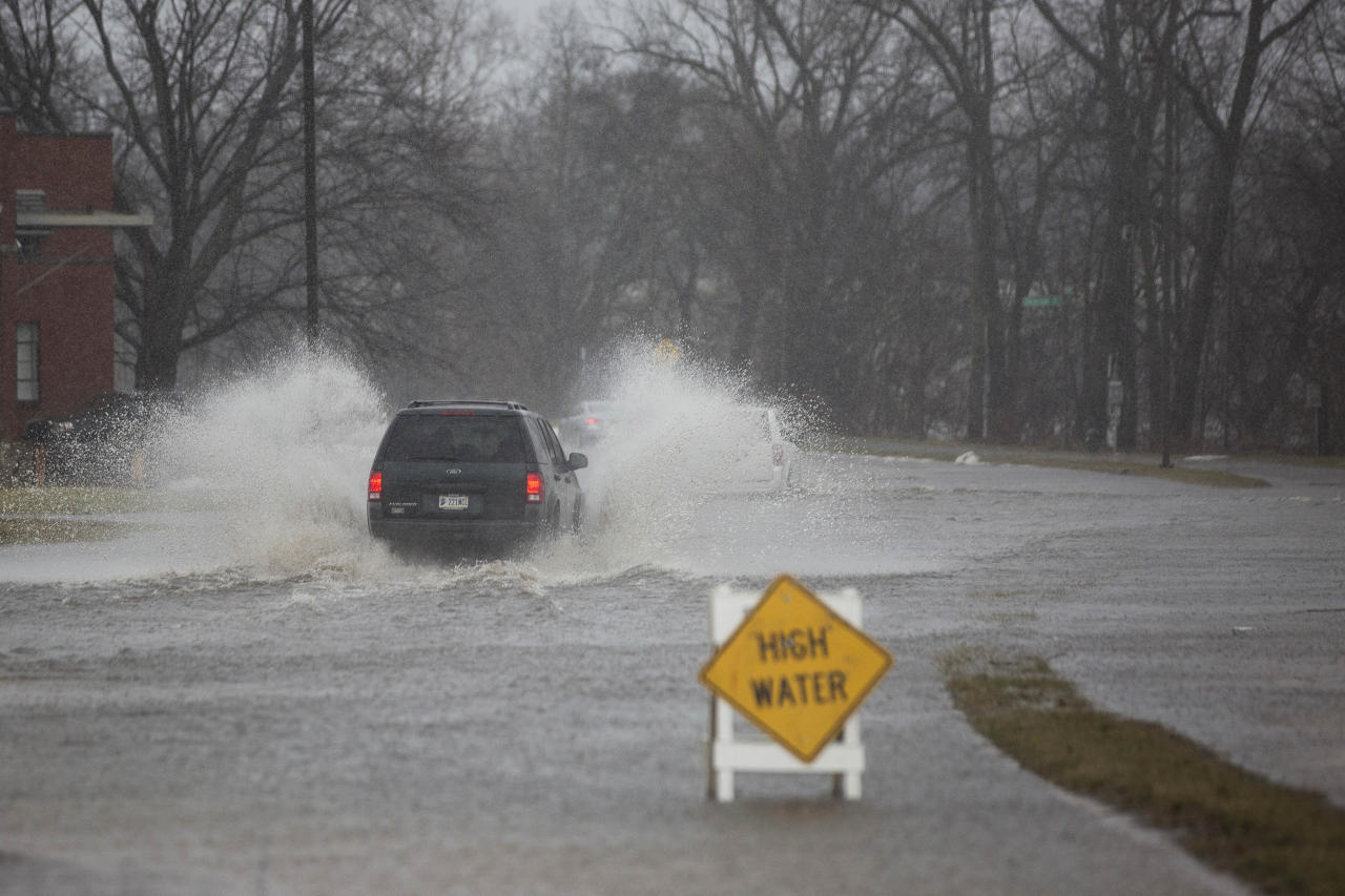 The driver of a car wades through an overflowing street in South Bend, Ind., Tuesday, Feb. 20, 2018. A storm system stretched from Texas to the Great Lakes states and forced some schools to close. The National Weather Service issued winter weather advisories for parts of Oklahoma, Kansas, North Dakota, Missouri, Iowa, Minnesota and Wisconsin. Flood warnings were in effect in Illinois, Indiana and Michigan with flood watches in Texas and Arkansas. (Santiago Flores/South Bend Tribune via AP)