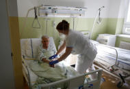 Karolina Repikova, a 22-year-old student at a vocational school, tends to a patient at a hospital in Kyjov, Czech Republic, Thursday, Oct. 22, 2020. With cases surging in central Europe, some countries are calling in soldiers, firefighters, students and retired doctors to help shore up buckling health care systems. (AP Photo/Petr David Josek)