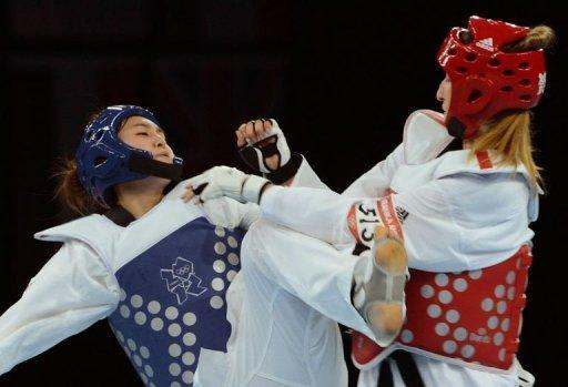 South Korea's Hwang Kyung-Seon (blue) fights against Slovenia's Franka Anic