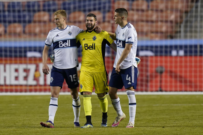 Vancouver Whitecaps' Andy Rose (15) and Ranko Veselinovic (4) celebrate with goalkeeper Maxime Crepeau (16) following their MLS soccer game against the Portland Timbers, Sunday, April 18, 2021, in Sandy, Utah. (AP Photo/Rick Bowmer)
