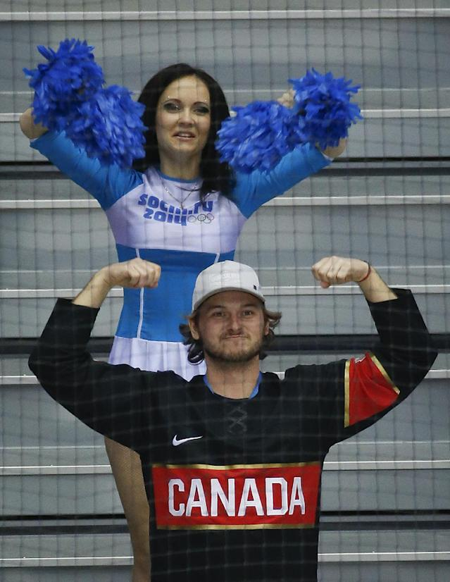 An Olympic cheerleader mimics a Canadian fan in the second period of a men's ice hockey game between Canada and Norway at the 2014 Winter Olympics, Thursday, Feb. 13, 2014, in Sochi, Russia. (AP Photo/Mark Humphrey)