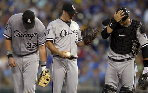 Chicago White Sox designated hitter Adam Dunn (32) stands with catcher Tyler Flowers, right, and starting pitcher Jake Peavy (44) while waiting for a pitching change in the eighth inning of a baseball game against the Kansas City Royals in Kansas City, Mo., Saturday, July 14, 2012. The Royals defeated the White Sox 6-3. (AP Photo/Orlin Wagner)