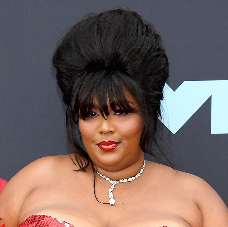 Lizzo's VMA hair is 100 percent that beehive. The first-time nominee arrived at the event in a towering updo with super-long bangs, looking like she's about to be crowned the winner of a beauty pageant.