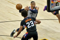 Washington Wizards guard Russell Westbrook (4) passes around Phoenix Suns forward Cameron Johnson (23) during the second half of an NBA basketball game, Saturday, April 10, 2021, in Phoenix. (AP Photo/Matt York)