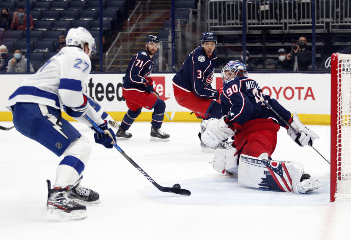 Tampa Bay Lightning defenseman Ryan McDonagh, left, shoots and scores against Columbus Blue Jackets goalie Elvis Merzlikins, right, during the first period an NHL hockey game in Columbus, Ohio, Thursday, April 8, 2021. (AP Photo/Paul Vernon)