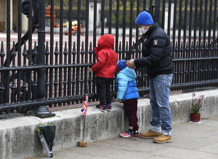 A child peers through the gates of Buckingham Palace in London, a day after the death of Britain's Prince Philip, Saturday, April 10, 2021. Britain's Prince Philip, the irascible and tough-minded husband of Queen Elizabeth II who spent more than seven decades supporting his wife in a role that mostly defined his life, died on Friday. (AP Photo/Alberto Pezzali)